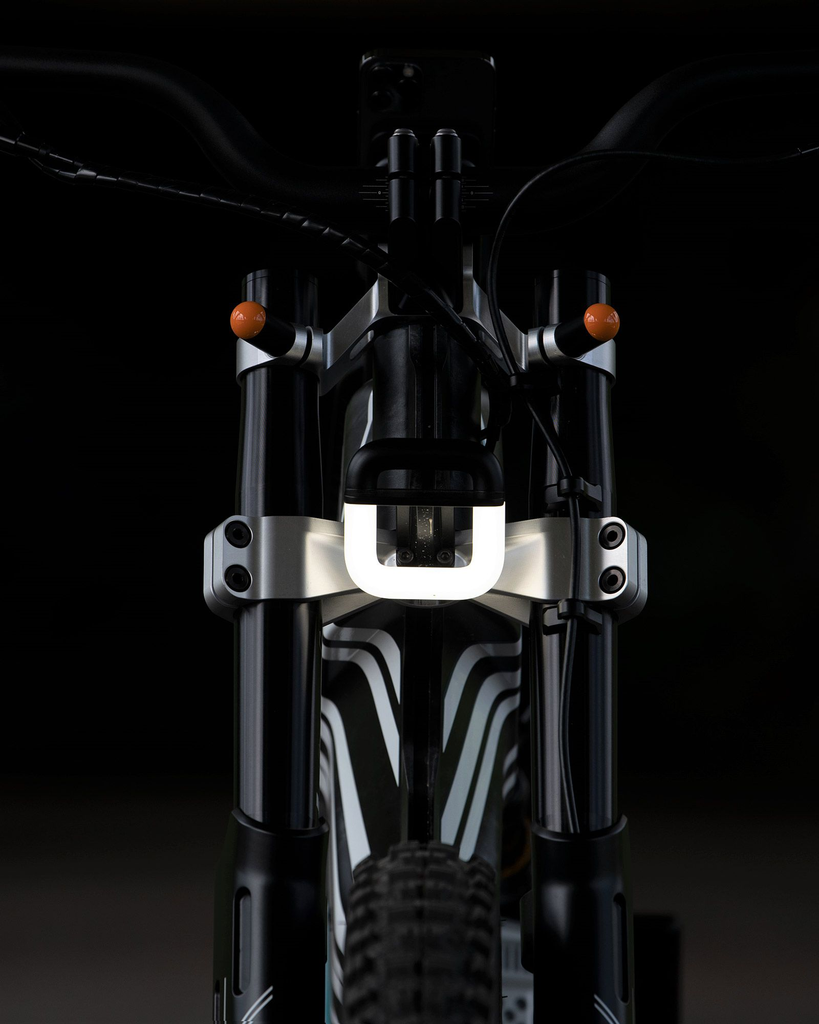 Beefy front fork holds a unique U-shaped LED lighting element as well as a 26-inch front wheel.